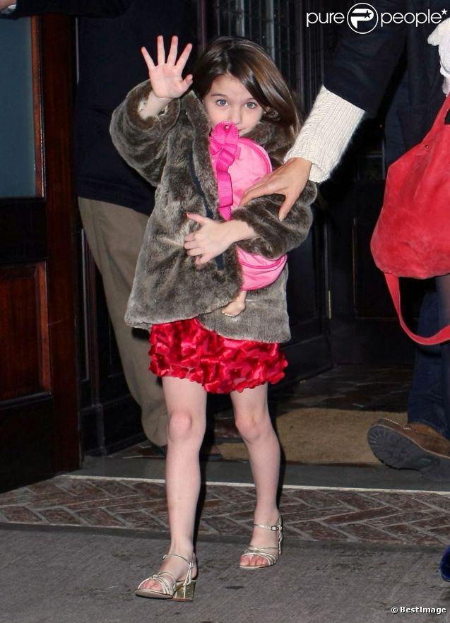 Suri Cruise fait coucou aux photographes en compagnie de sa maman Katie Holmes et Tom Cruise à New York le 20 décembre 2011