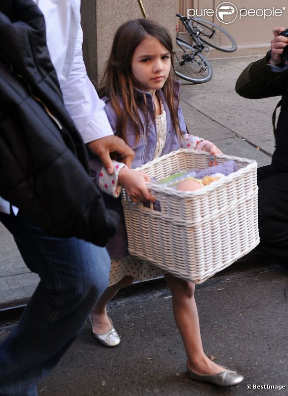 Suri Cruise sort de son appartement un panier dans les mains, à New York, le 26 mars 2012