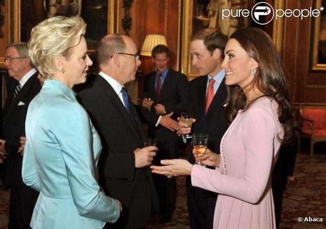 Catherine, duchesse de Cambridge, semble avoir trouvé en la princesse Charlene de Monaco, élégante en tailleur Dior, une interlocutrice plaisante lors du déjeuner donné par Elizabeth II à Windsor pour son jubilé de diamant en présence de 26 souverains, le 18 mai 2012.