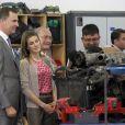 """""""A a découverte d'un atelier de mécanique... Inspirée, Letizia ? Felipe et Letizia d'Espagne visitaient à Malaga un programme de l'initiative Caritas financée par la Fondation Hesperia, le 22 mai 2012, jour de leurs 8 ans de mariage."""""""