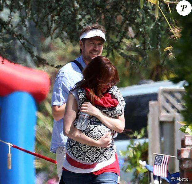 Alyson Hannigan protège sa petite Keeva Kane des photographes aux côtés de son mari Alexis Denisof lorsqu'ils célèbrent le 4 juillet avec leurs filles Satyana et Keeva à Brentwood le 4 juillet 2012