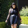 Kim Kardashian, enceinte et tout de noir vêtue avec un chemisier transparent, une jupe en cuir et des souliers Jimmy Choo, quitte sa maison. Beverly Hills, le 28 mars 2013.