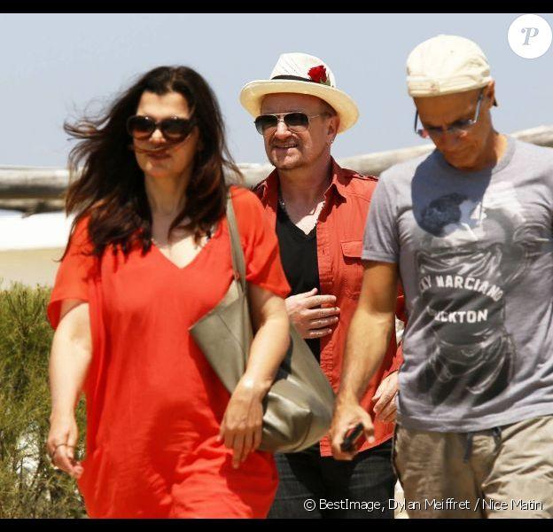 Le chanteur Bono, sa femme Alison Hewson (en robe rouge) et Larry Mullen (batteur du groupe U2, chemise bleue à carreaux) arrivent au Club 55, plage de Pampelonne à Ramatuelle, le 04 juillet 2013.