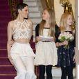 Jessie J se met à hauteur de la jeune Arabella Mansfield, chargée de remettre les programmes au prince Charles et à la duchesse Camilla, au moment de leur arrivée à la Royal Variety Performance du 25 novembre 2013 au Palladium, à Londres.