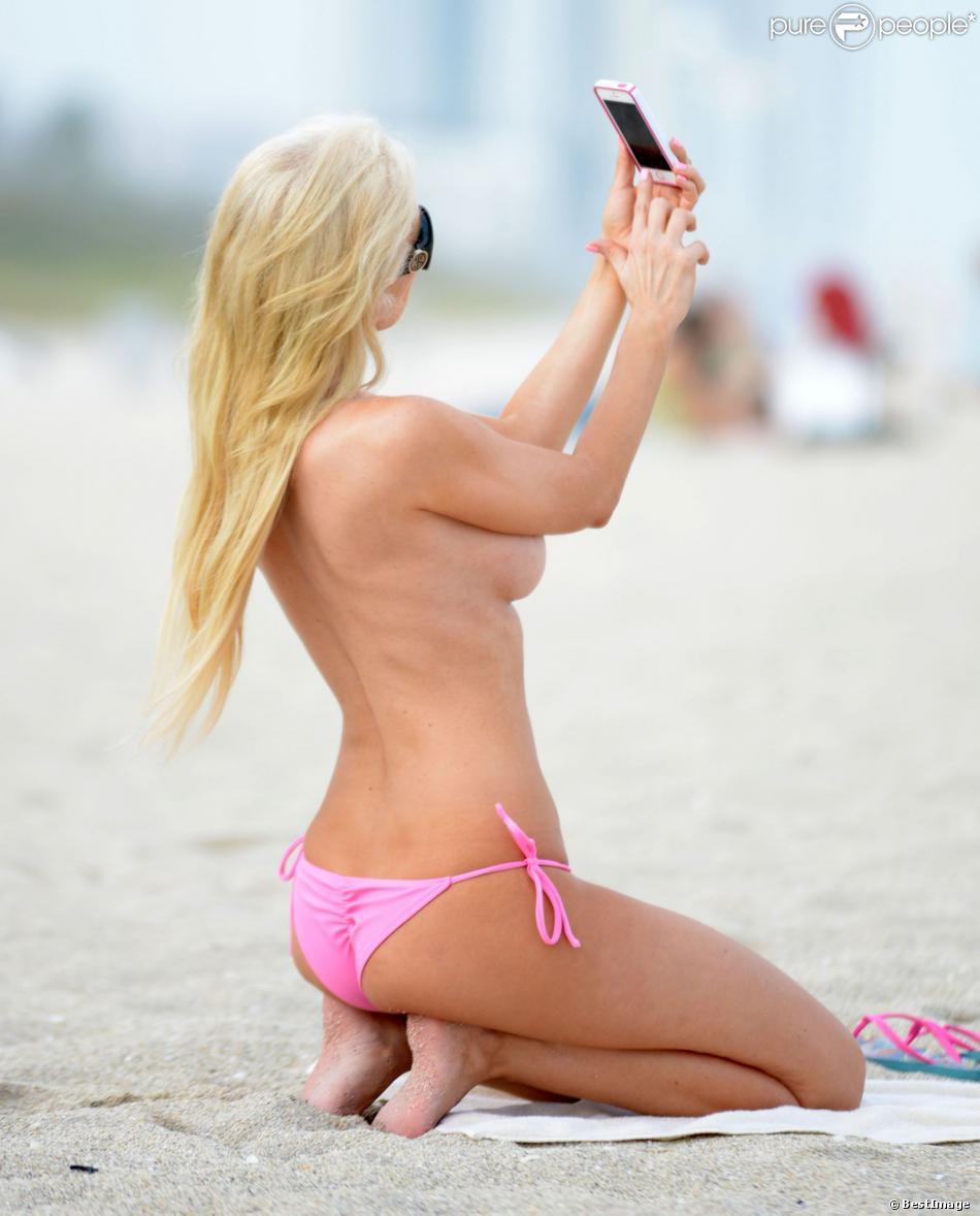 Exclusif - Ana Braga se prend en photo sur la plage à Miami, le 19 février 2014. Le selfie topless, tout un art.