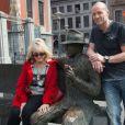 """Exclusif - Mylène Demongeot et Pierre Simenon (Frère de Marc Simenon, le mari de Mylène Demongeot, et fils cadet de Georges Simenon, et auteur du livre """"Au nom du sang versé"""") posent avec la statue de Georges Simenon sur un banc dans les rues de Liège, le 27 avril 2014."""