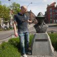 """Exclusif - Pierre Simenon (Fils cadet de Georges Simenon et frère de Marc Simenon, le mari de Mylène Demongeot, et auteur du livre """"Au nom du sang versé"""") pose avec la statue de Georges Simenon sur un banc dans les rues de Liège, le 27 avril 2014."""