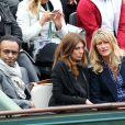 Manu Katché, sa compagne Laurence et Isabelle Camus, compagne de Yannick Noah aux Internationaux de France de tennis de Roland Garros à Paris, le 27 mai 2014, pendant le match de Gaël Monfils.