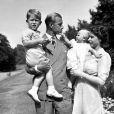 La princesse Anne enfant dans les bras de la reine Elizabeth II en 1951. Le prince Philip tient lui le prince Charles, à Clarence House.