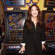 """Lynda Carter pose à côté de la nouvelle machine à sous """"Wonder-Woman"""" à Las Vegas, le 30 septembre 2014."""