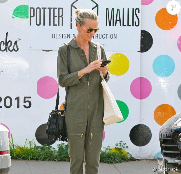 Laeticia Hallyday se rend au spa Caudalie à Venice. Des lunettes de soleil, un sac (modèle Petit Sac Emmanuelle) et des bottines Saint Laurent complètent sa combinaison kaki. Le 1er février 2015.