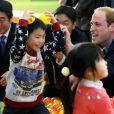 Le prince William lors d'une séance de jeu avec des enfants, en présence du Premier ministre nippon Shinzo Abe, le 28 février 2015 dans un centre de loisirs de Koriyama, lors de sa visite officielle au Japon.