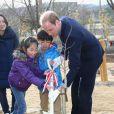 Le prince William plantant un arbre avec des enfants le 28 février 2015 dans un centre de loisirs de Koriyama, lors de sa visite officielle au Japon.