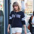"""Taylor Swift fait une cure de shopping à Studio City, le 10 mars 2015. Elle port un short blans et un pull sur lequel on peut lire """"New York""""."""