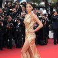 """Irina Shayk, exquise en robe dorée Versace, monte les marches du Palais des Festivals avant la projection du film en compétition """"Sicario à Cannes, le 19 mai 2015."""