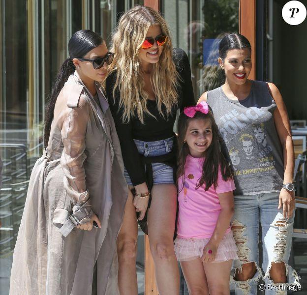 Les soeurs Kim, Khloé et Kourtney Kardashian, sollicitée par une jeune admiratrice, posent pour une photo souvenir devant le restaurant Hugo's à Ahoura Hills, le 14 juillet 2015.