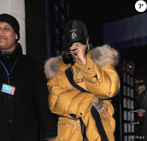 Rihanna quitte le Tramp à Londres, habillée d'un duffle-coat jaune Burberry et d'une robe en soie Rosetta Getty. Une casquette à l'effigie de la boîte de nuit londonienne Tramp et des lunettes de soleil Adam Selman x Le Specs accessoirisent sa tenue. Le 24 février 2016.