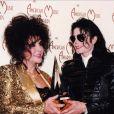"""""""Elizabeth Taylor et Michael Jackson tiennent un trophée des American Music Awards en forme de pyramide transparente. La cérémonie est-elle organisée par les Illuminati ? Los Angeles, mars 2003."""""""