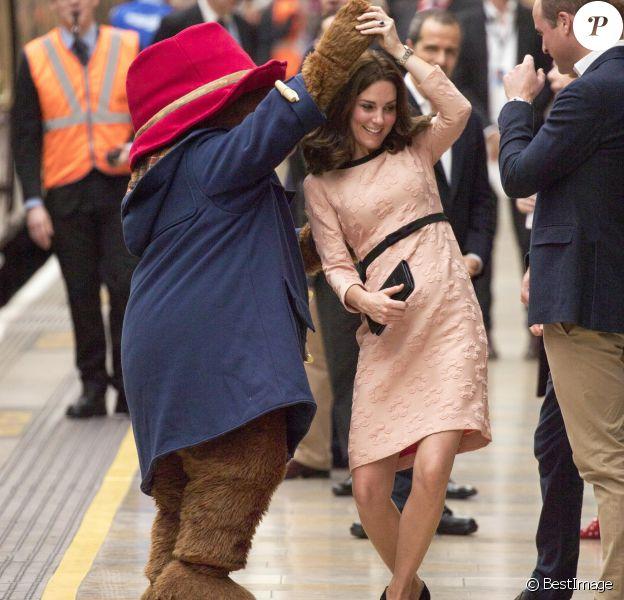Kate Middleton, enceinte et vêtue d'une robe Orla Kiely, s'est laissé entraîner dans une danse par l'ours Paddington sur le quai de la gare de Paddington, à Londres le 16 octobre 2017, lors d'un événement du Charities Forum auquel elle prenait part avec le prince William et le prince Harry.
