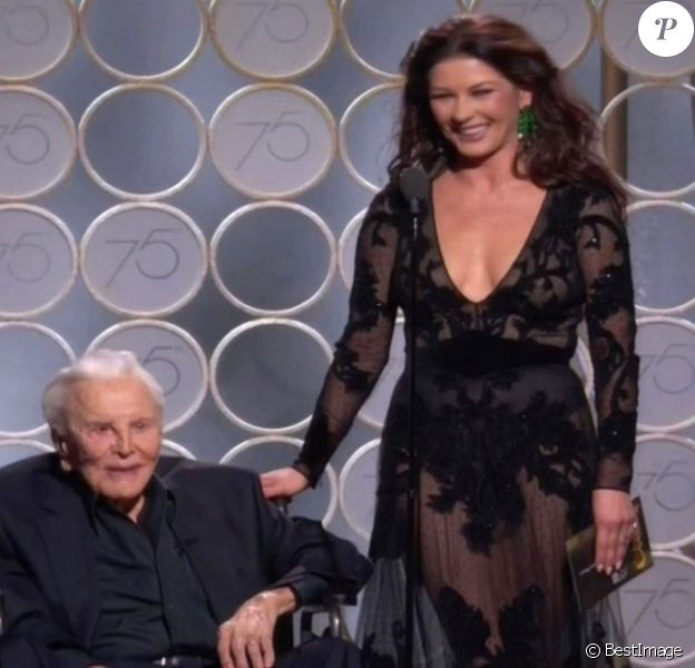 """Kirk Douglas (101 ans) sur scène avec sa belle-fille Catherine Zeta-Jones pour présenter le Golden Globe du meilleur scénario lors de la 75ème cérémonie annuelle des Golden Globe Awards au Beverly Hilton Hotel à Los Angeles, le 7 janvier 2018. Kirk et Catherine étaient devant un parterre de stars, toutes levées pour accueillir et acclamer la légende du cinéma. Catherine a rendu hommage à son beau-père lors d'un discours.  Los Angeles, CA - Hollywood legend Kirk Douglas, 101, gets a standing ovation as he steals the show with daughter-in-law Catherine Zeta Jones at Golden Globes. Douglas took to the stage in a wheelchair with Zeta Jones, to present the award for Best Screenplay for a Motion Picture. Zeta Jones, the wife of Kirk's actor son, paid tribute to her father-in-law's career. """"In 1991 my father in law, this living Hollywood legend Kirk, was recognised by the Writer's Guild Of America for his role in ending the Hollywood Blacklist,"""" she said. The blacklist saw entertainment professionals denied work because they were accused of having Communist ties. She reminded the audience how Kirk hired the screenwriter D. Trumbo to write the Hollywood epic Spartacus and insisted his name appear as writer. Kirk responded to Zeta Jones' words, although most of his speech was inaudible. """"Catherine,"""" he said. """"You said it all. I would have made a speech. I wanna say that...."""" He paused, and added with a smile: """"I can never follow you."""" Replied the actress, holding his hand: """"Why don't we say that here are the nominations?"""" Zeta Jones then read out of the nominations before announcing the winner.07/01/2018 - Los Angeles"""