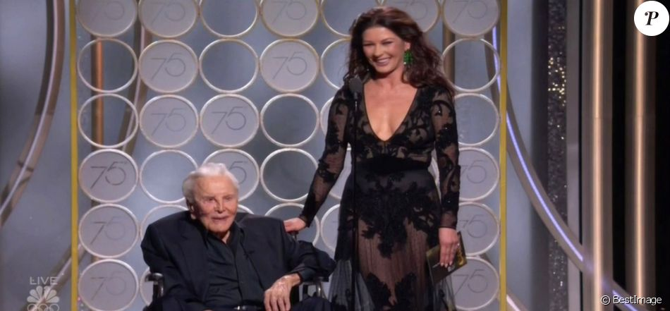 "Kirk Douglas (101 ans) sur scène avec sa belle-fille Catherine Zeta-Jones pour présenter le Golden Globe du meilleur scénario lors de la 75ème cérémonie annuelle des Golden Globe Awards au Beverly Hilton Hotel à Los Angeles, le 7 janvier 2018. Kirk et Catherine étaient devant un parterre de stars, toutes levées pour accueillir et acclamer la légende du cinéma. Catherine a rendu hommage à son beau-père lors d'un discours.  Los Angeles, CA - Hollywood legend Kirk Douglas, 101, gets a standing ovation as he steals the show with daughter-in-law Catherine Zeta Jones at Golden Globes. Douglas took to the stage in a wheelchair with Zeta Jones, to present the award for Best Screenplay for a Motion Picture. Zeta Jones, the wife of Kirk's actor son, paid tribute to her father-in-law's career. ""In 1991 my father in law, this living Hollywood legend Kirk, was recognised by the Writer's Guild Of America for his role in ending the Hollywood Blacklist,"" she said. The blacklist saw entertainment professionals denied work because they were accused of having Communist ties. She reminded the audience how Kirk hired the screenwriter D. Trumbo to write the Hollywood epic Spartacus and insisted his name appear as writer. Kirk responded to Zeta Jones' words, although most of his speech was inaudible. ""Catherine,"" he said. ""You said it all. I would have made a speech. I wanna say that...."" He paused, and added with a smile: ""I can never follow you."" Replied the actress, holding his hand: ""Why don't we say that here are the nominations?"" Zeta Jones then read out of the nominations before announcing the winner.07/01/2018 - Los Angeles"