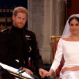 Mariage du prince Harry et de Meghan Markle le 19 mai 2018, main dans la main en la chapelle St George à Windsor. Meghan porte une robe de mariée confectionnée par Clare Waight Keller pour Givenchy, Harry porte son uniforme de capitaine des Blues and Royals.