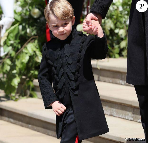 """Le prince George de Cambridge, petit """"pageboy"""" vêtu d'une réplique de l'uniforme des Blues and Royals porté par le prince Harry et le prince William, au mariage du prince Harry et de Meghan Markle, à la sortie de la chapelle St George à Windsor le 19 mai 2018."""