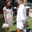 La duchesse Catherine de Cambridge (Kate Middleton) et la duchesse Meghan de Sussex (Meghan Markle) saluent le staff qui officiera lors de la finale dames, à Wimbledon le 14 juillet 2018, quelques dizaines de minutes avant le début de la finale opposant Serena Williams et Angelique Kerber.