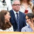 La duchesse Catherine de Cambridge (Kate Middleton) et la duchesse Meghan de Sussex (Meghan Markle) complices dans la royal box à Wimbledon le 14 juillet 2018.