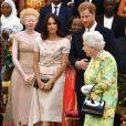 """Meghan Markle en Prada avec la reine Elizabeth II et le prince Harry à la cérémonie """"Queen's Young Leaders Awards"""" au palais de Buckingham, à Londres, le 26 juin 2018. Un ensemble à double boutonnage plutôt classique, qui n'est pas sans rappeler le style de Jackie Kennedy."""