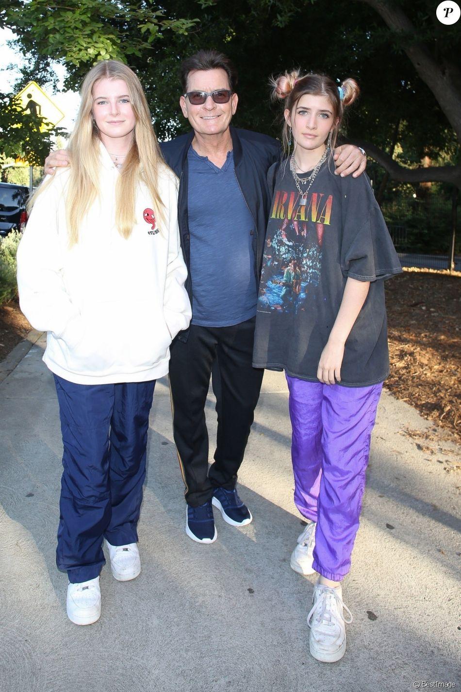 Charlie Sheen pose avec ses filles alors qu'il arrive au concert de Billie Eilish au théâtre Greek à Los Angeles, le 11 juillet 2019.