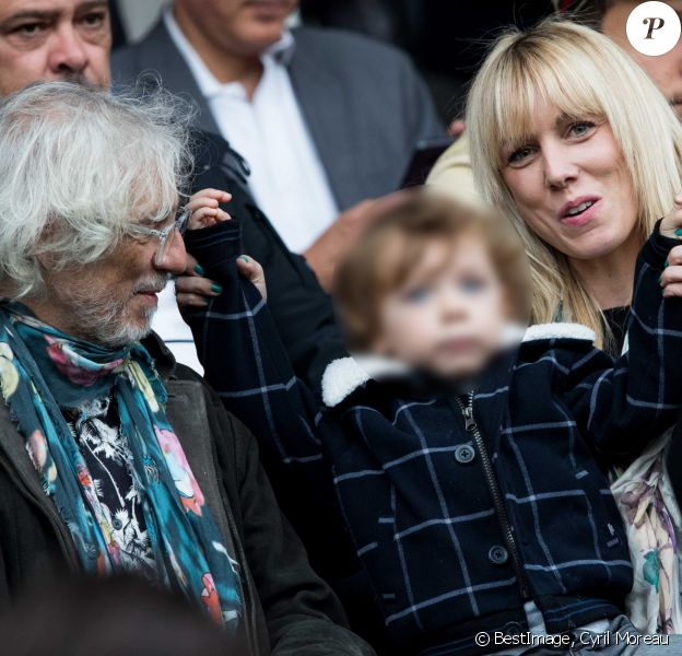 "Louis Bertignac avec sa compagne Laetitia et leur fils Jack dans les tribunes lors du match de Ligue 1 ""PSG - Angers (4-0)"" au Parc des Princes à Paris, le 5 octobre 2019. © Cyril Moreau/Bestimage"