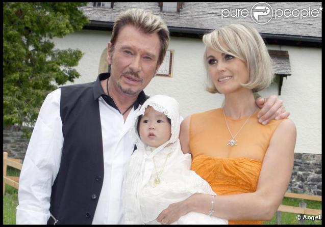 Johnny et Laeticia Hallyday avec Joy au cours du baptême de cette dernière à Gstaad en Suisse le 5 juillet 2009