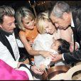 Johnny et Laeticia Hallyday avec leurs filles Jade et Joy au cours du baptême de cette dernière à Gstaad en Suisse le 5 juillet 2009 : ici avec le parrain Jean-Claude Darmon et la marraine Hélène Darroze