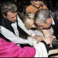 Johnny et Laeticia Hallyday avec au cours du baptême de Joy à Gstaad en Suisse le 5 juillet 2009 : ici avec le parrain Jean-Claude Darmon et la marraine Hélène Darroze