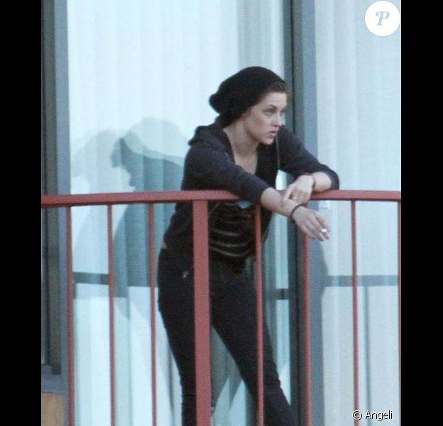 De retour à son hôtel après une balade sur un bateau, Kristen Stewart fume une cigarette sur le balcon de sa chambre... et adresse un petit signe gracieux aux photographes, le dimanche 30 mai à Sydney, en Australie.