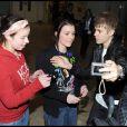 Justin Bieber arrive à l'aéroport de Londres-Heathrow, jeudi 3 mars, et prend le temps de faire quelques photos avec ses fans venus l'accueillir sur place.