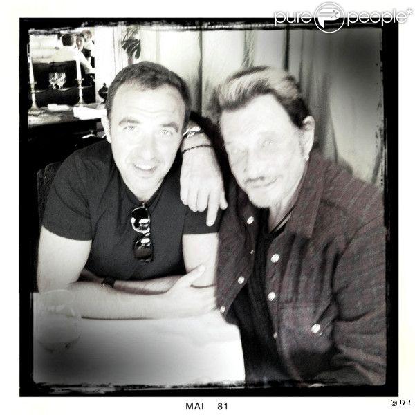 Johnny Hallyday et Nikos Aliagas posent au restaurant Le Murat, à Paris, le 10 mai 2011.