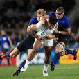 Rougerie et Harinordoquy tombent sur le râble de Tuilagi.   Le XV de France a su se transcender et retrouver les valeurs du combat pour dominer (19-12) le XV de la Rose le 8 octobre 2011 et accéder aux demi-finales du Mondial de rugby 2011.
