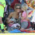 Denise Richards donne le biberon à Eloise auprès de Lola devant le match de sa fille aînée Sam à San Fernando Valley le 29 octobre 2011