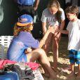 Rihanna se pose quelques minutes pour discuter avec deux enfants à la Barbade le 29 décembre 2011