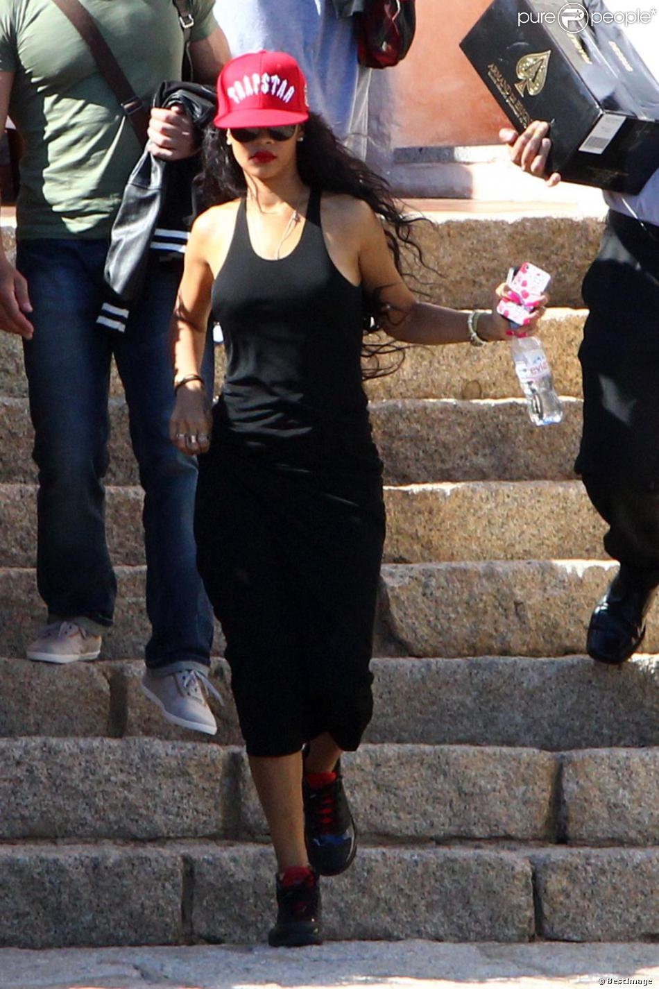 Rihanna, habillée d une casquette Trapstar, d une robe noire et de baskets  Air Jordan, sort de son hôtel, le Cala Di Volpe. Porto Cervo, le 15 juillet  2012. 3a928e49f461