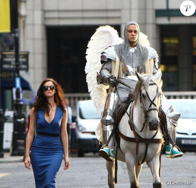 Robbie Williams en chevalier, avec Kaya Scodelario. Tournage de son nouveau clip le 17 août 2012 à Londres, avec la participation de la jeune actrice Kaya Scodelario, star de la série Skins.