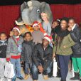 Adriana Karembeu au cirque Pinder pour l'opération  Tous en fête ! 2012 . Le 12 décembre 2012. Elle prend la pose avec des enfants.