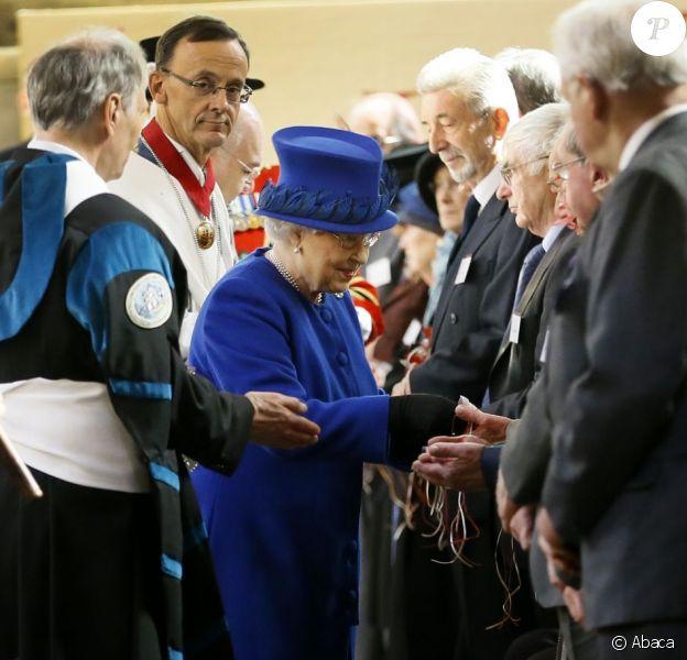 La reine Elizabeth II le 28 mars 2013 à Oxford, accompagnée de son époux le duc d'Edimbourg, distribuant de l'argent comme le veut la tradition lors de la messe de célébration du Jeudi saint.