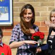 """ Kate Middleton, enceinte de 6 mois, visitait le 23 avril 2013 l'école The Willows de Wythenshawe, dans la région de Manchester, pour la promotion du programme M-PAC, soutenu par la Fondation du duc et de la duchesse de Cambridge et du prince Harry, mais aussi Place2Be et Action on Addiction, deux associations dont elle assume le patronage. """