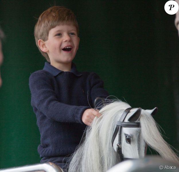 James, vicomte Severn, fils du prince Edward et de la comtesse Sophie de Wessex, s'éclate sur des chevaux de bois au Windsor Horse Show le 11 mai 2013