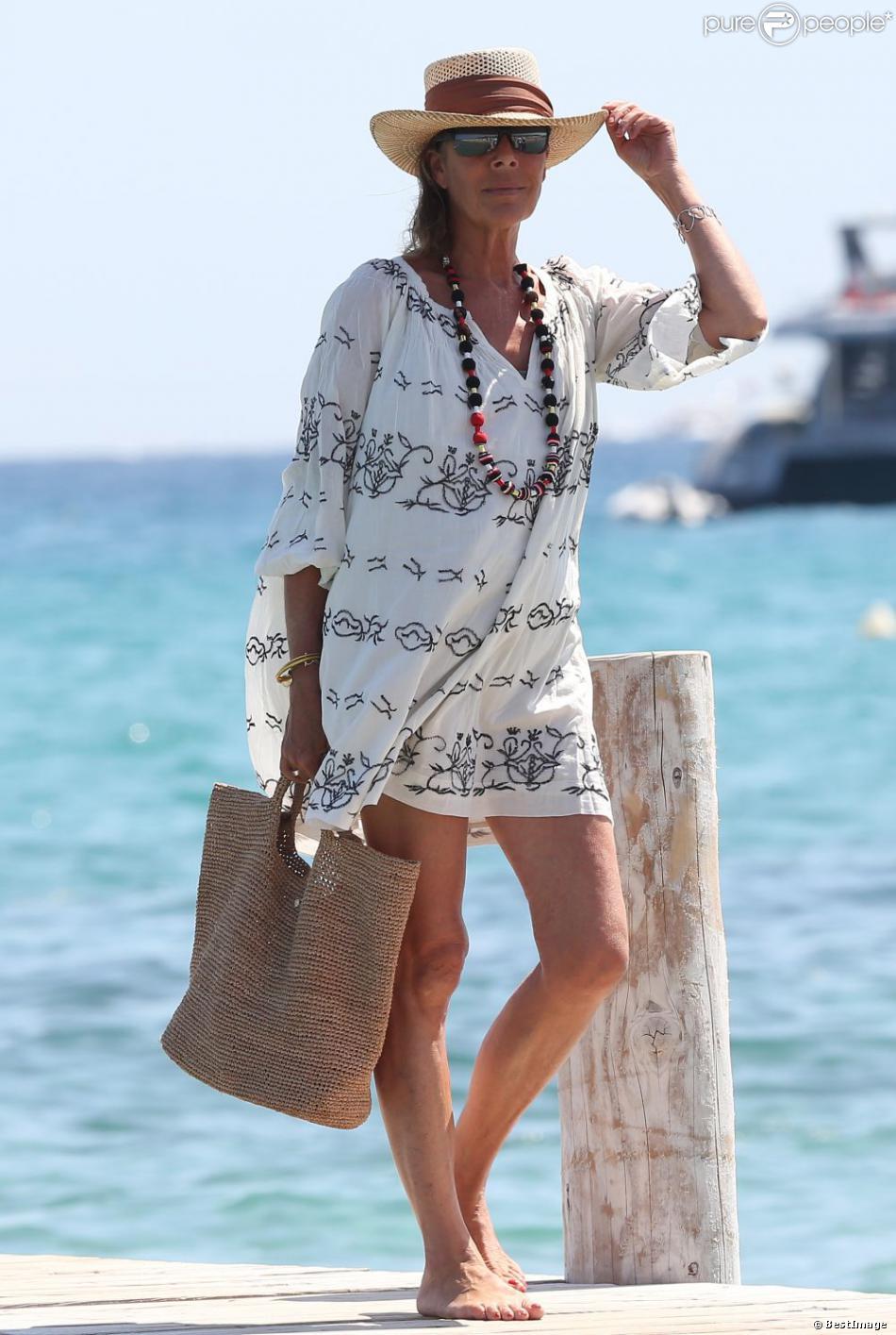 La princesse Caroline de Hanovre, superbe en tunique estivale, arrive au Club 55 à Saint-Tropez, avec des amis, le 23 août 2013.