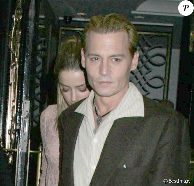 L'acteur américain Johnny Depp, teint en blond, et sa compagne Amber Heard sortant du restaurant Ronnie Scott à Londres, le 25 octobre 2013