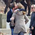 Chris O'Neill embrassant la princesse Madeleine de Suède, son épouse, dans Central Park le 22 mars 2014 à New York lors d'une promenade avec leur fille Leonore et des amis.